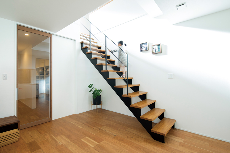 黒いアイアンと手すりと木目のステップが印象的なリビング階段