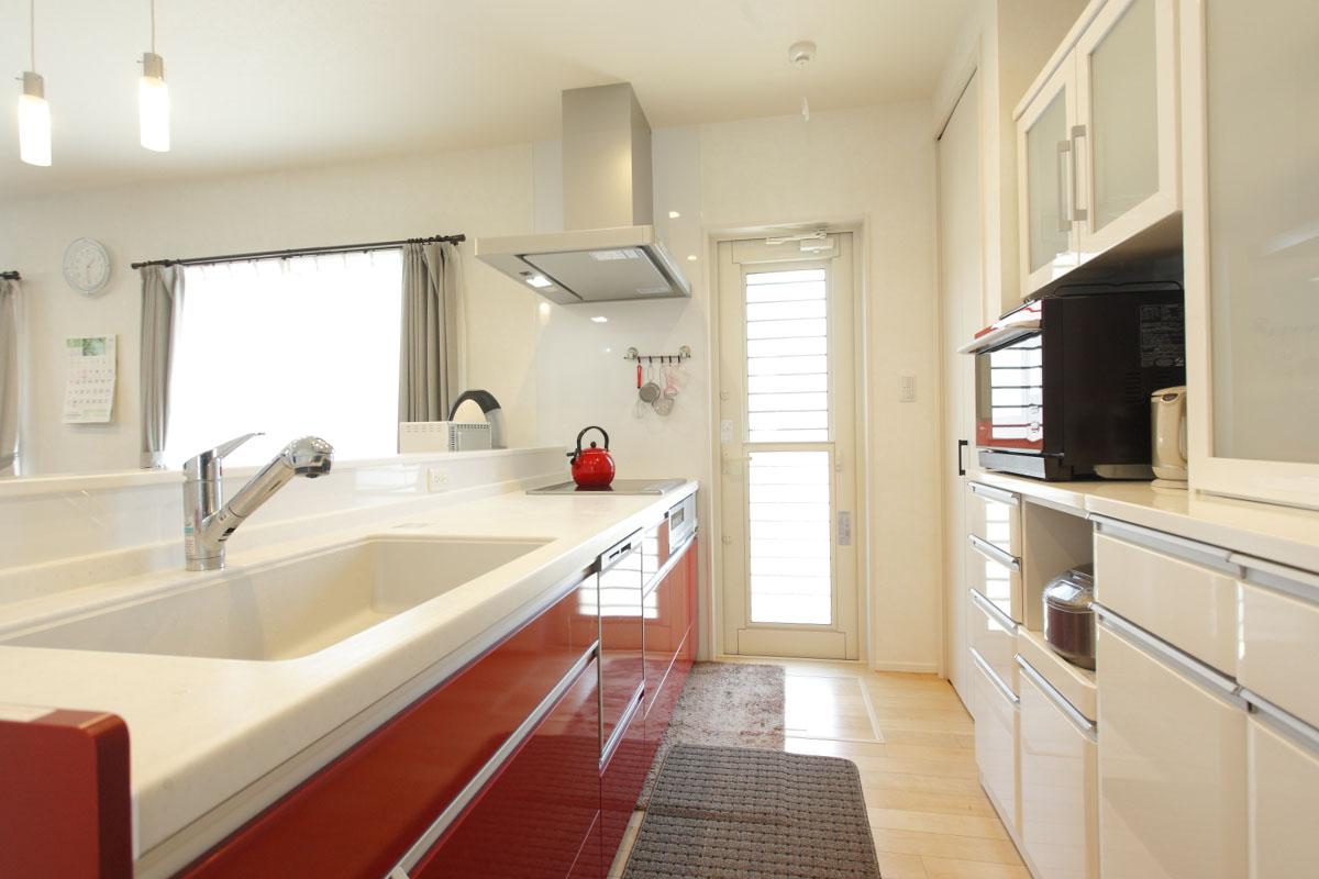 赤色を取り入れたキッチンは、対面式を採用。さらにパントリーを設置し、収納力も充実。
