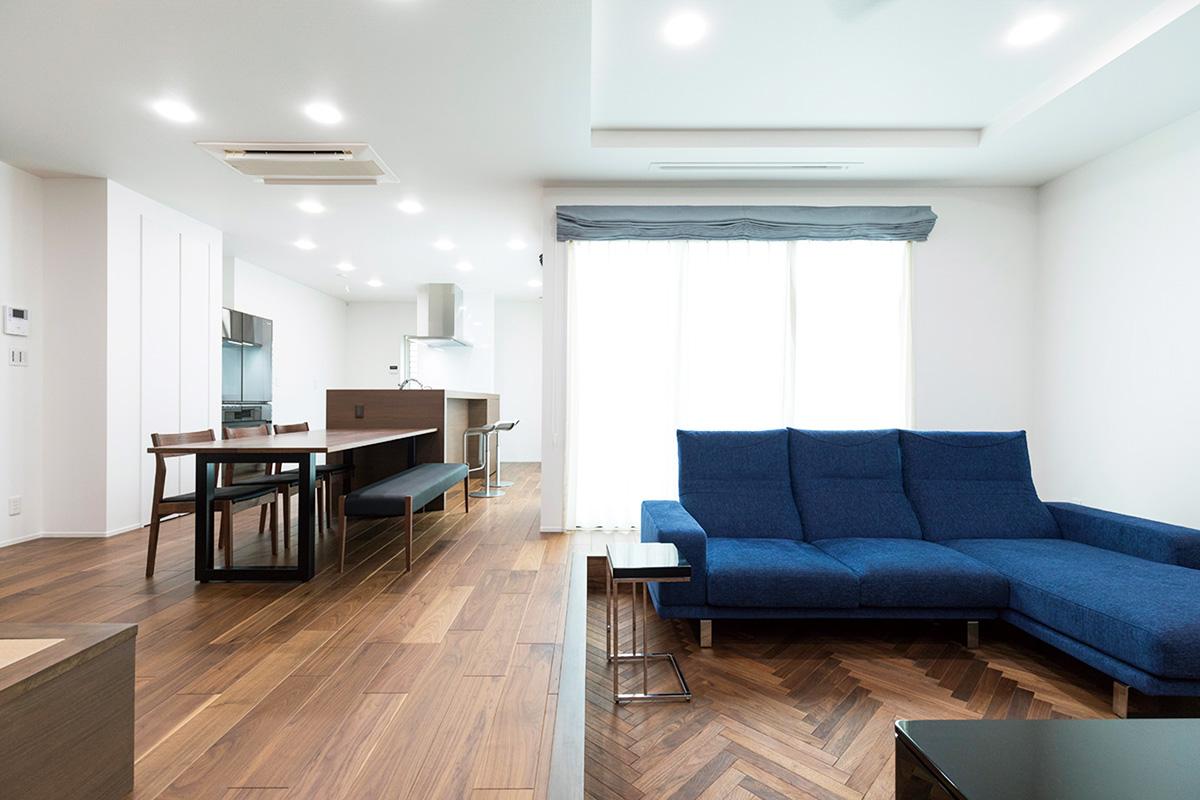 リビングはご家族が集まる憩いの場として、建具で仕切らないスキップフロアに。  下段の床材はモダンなデザインのヘリンボーンを使い、視覚的にも層で変化をつけています。  リビングの顔となるソファは奥さまの好きなネイビーをセレクトして、上質で開放的な空間にアクセントを効かせた仕上がりになりました。