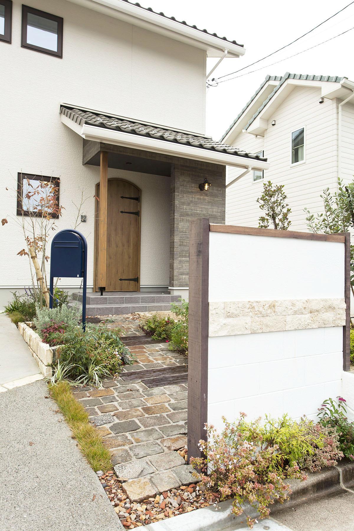 玄関までのアプローチはご主人がイラストを描き、デザインしたそう。脇を固めるクレイチップが個性的です。