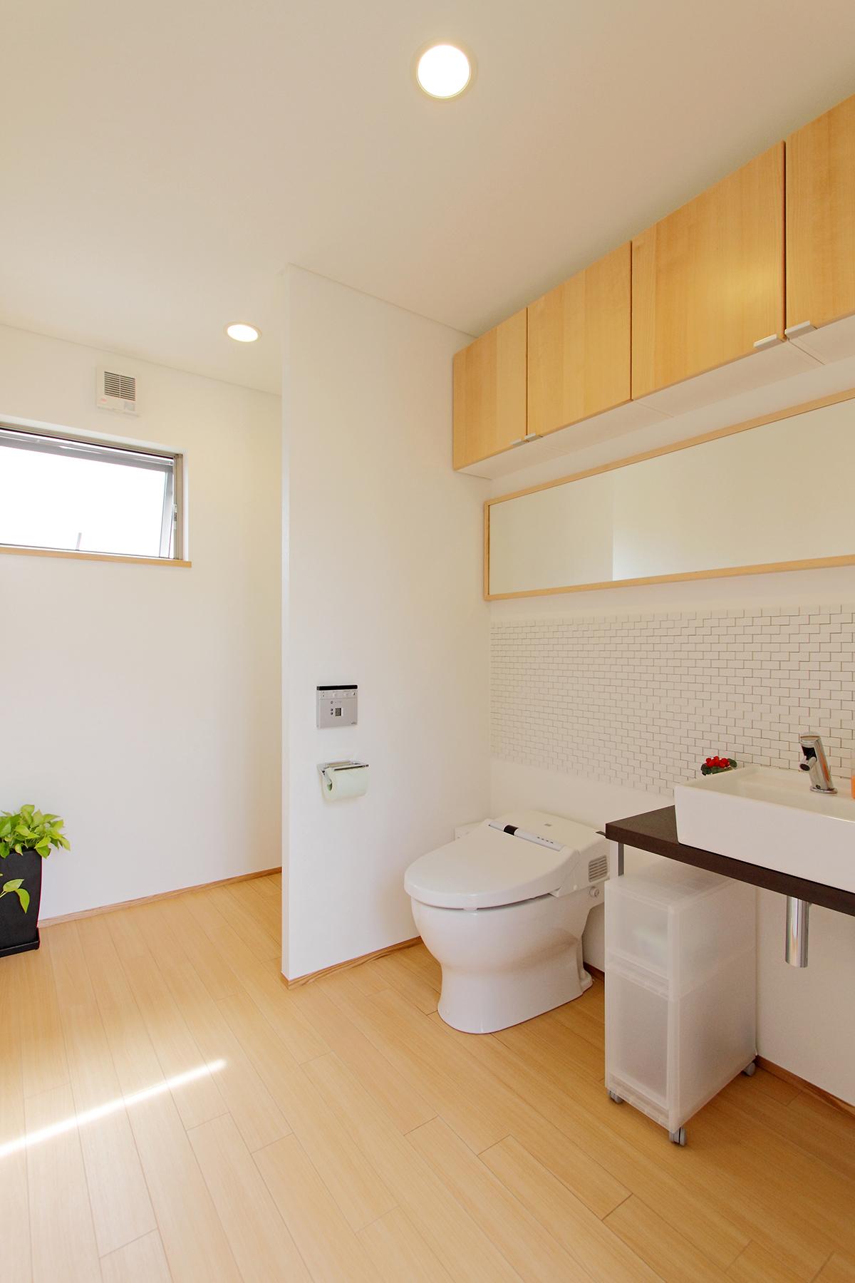 ゆったりとしたトイレ。壁に張ったタイルが空間にアクセントをプラス。