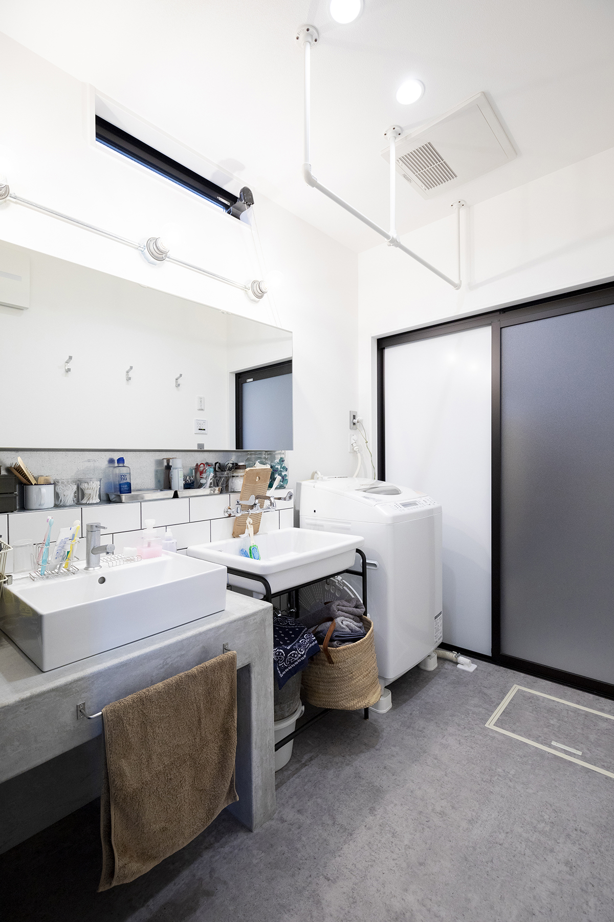 配管を活かした照明を取り入れるなど、アイデア満載な造作洗面台。