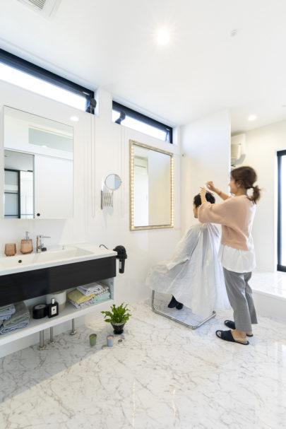 大理石調のタイルを敷き詰めた、広々と明るい洗面室。美容師である奥さまが、ご主人さまの髪をカットされます。