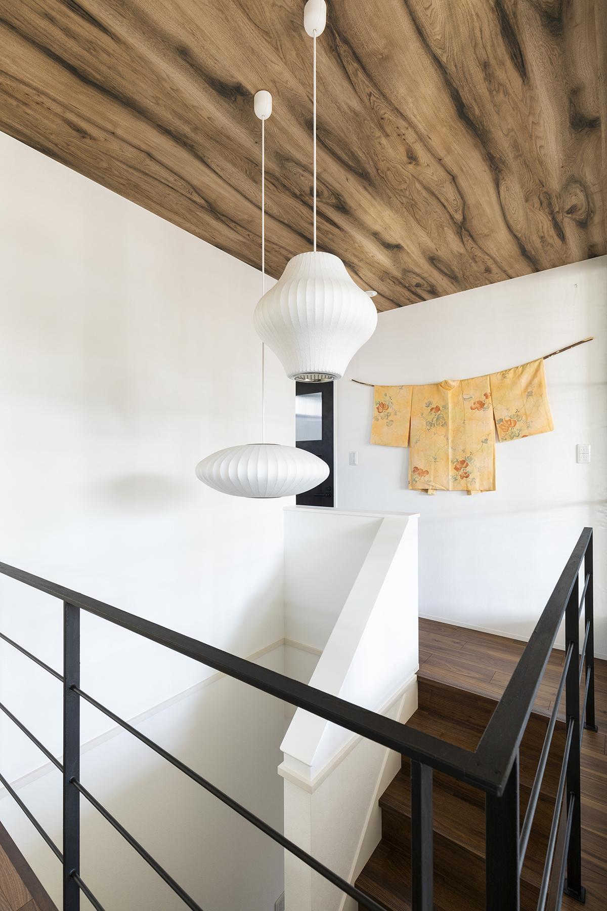 木肌の天井と和紙の照明、アイアンが調和する印象的な階段ホール。壁には奥さまがリメイクした昔の着物を飾り、季節の趣を演出。