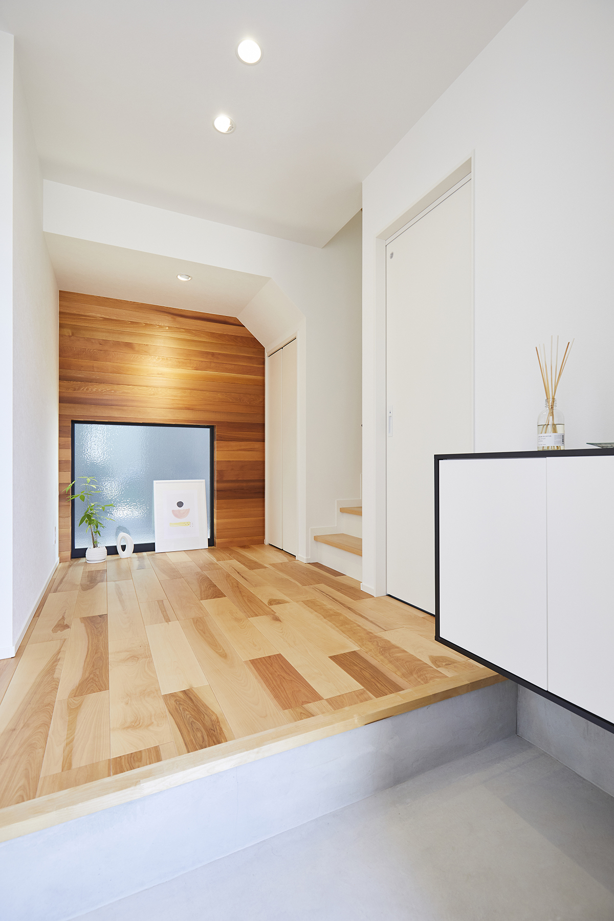 床面に面した窓と木目調の壁が印象的な玄関ホール。