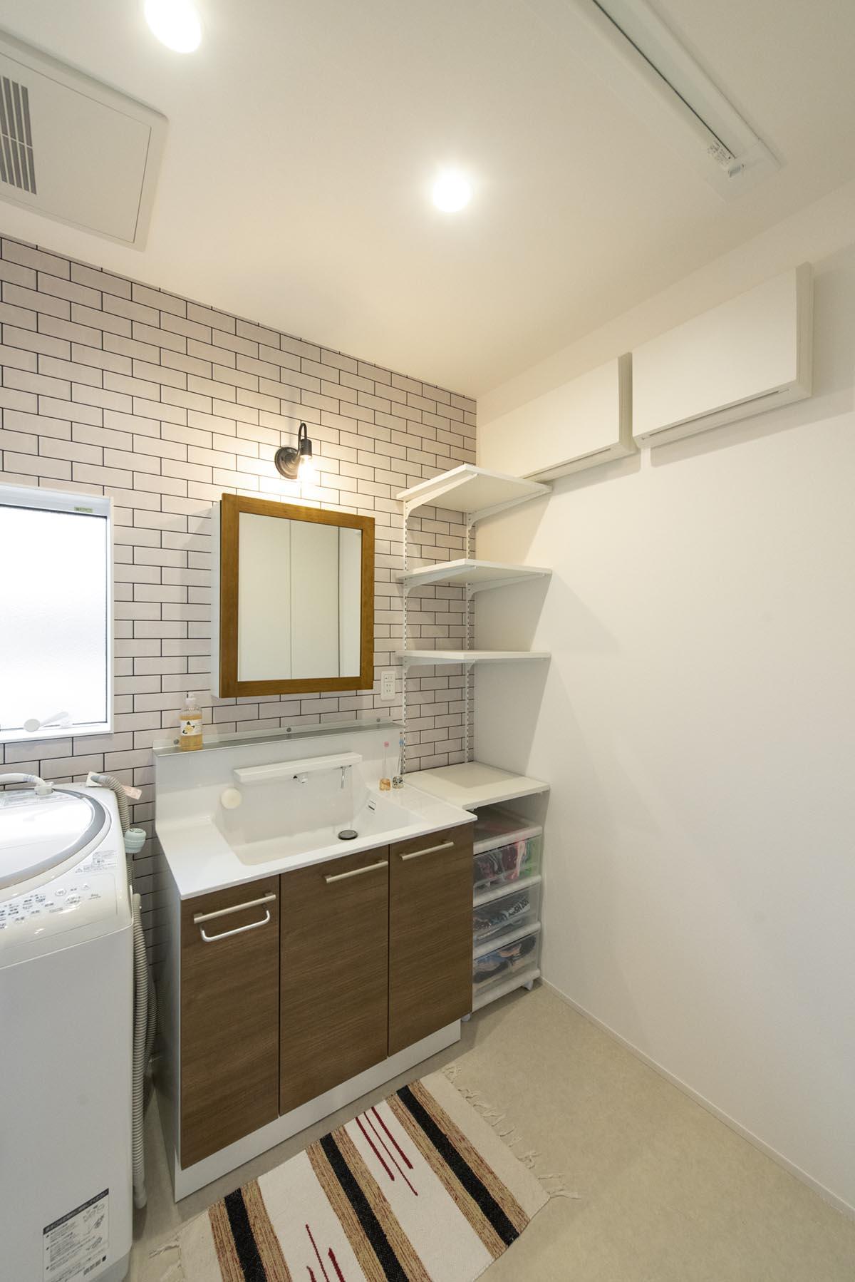 洗面ボウル、カウンター部分はメーカー既製品を使用し、ミラー部分をナチュラルにアレンジ。壁面のタイル貼りがかわいく、入る度に楽しくなるスペースです。実用性も考えて可動棚を設置しています。