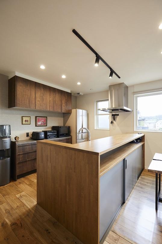 周りの木目に合わせてキッチンの色味も統一。キッチン反対側にはニッチと収納スペースを設けて、スッキリした水回りに。