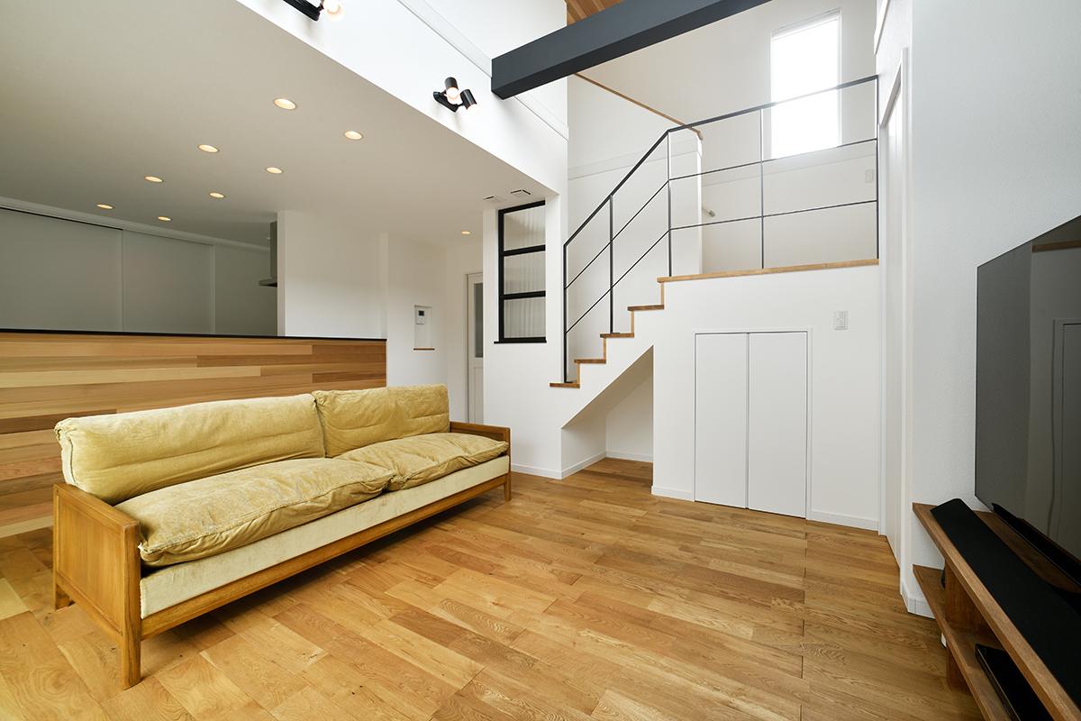 吹き抜けがあり広々と感じるLDK。無垢床・キッチンと天井の板張りがモダンな雰囲気のポイントに。